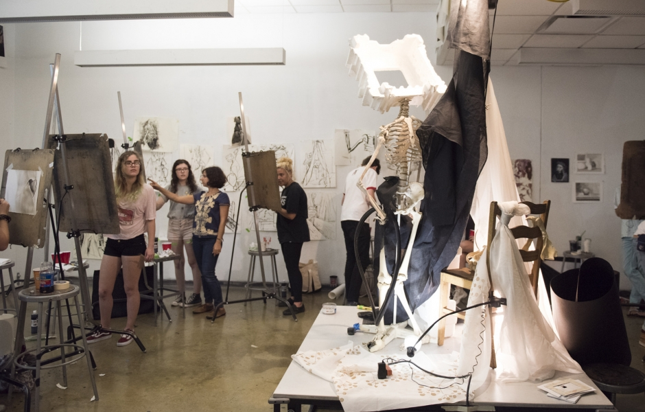 Professor with students in drawing studio.
