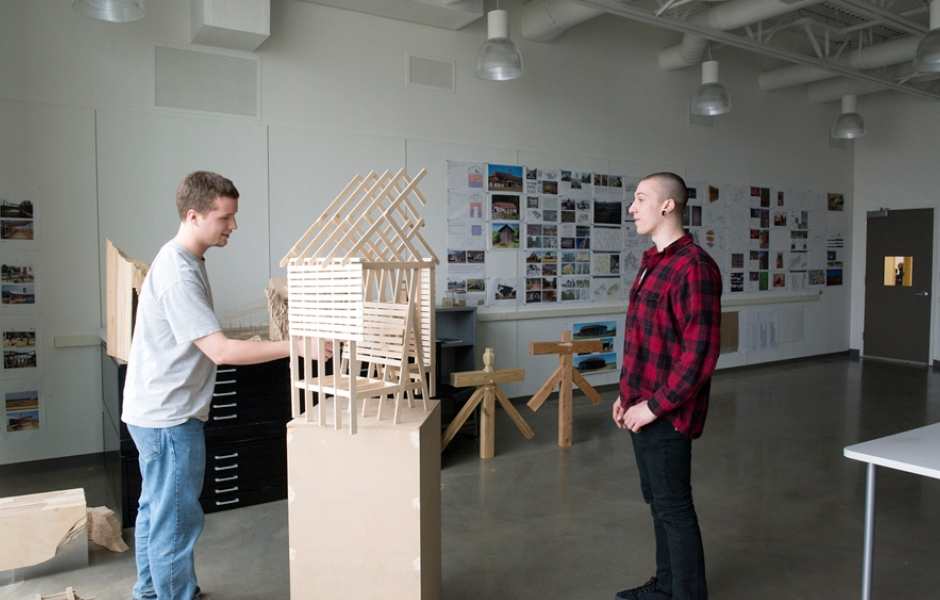 two male students discussing wooden model