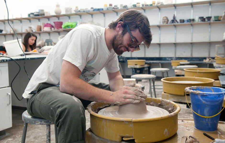 male student working with clay on wheel