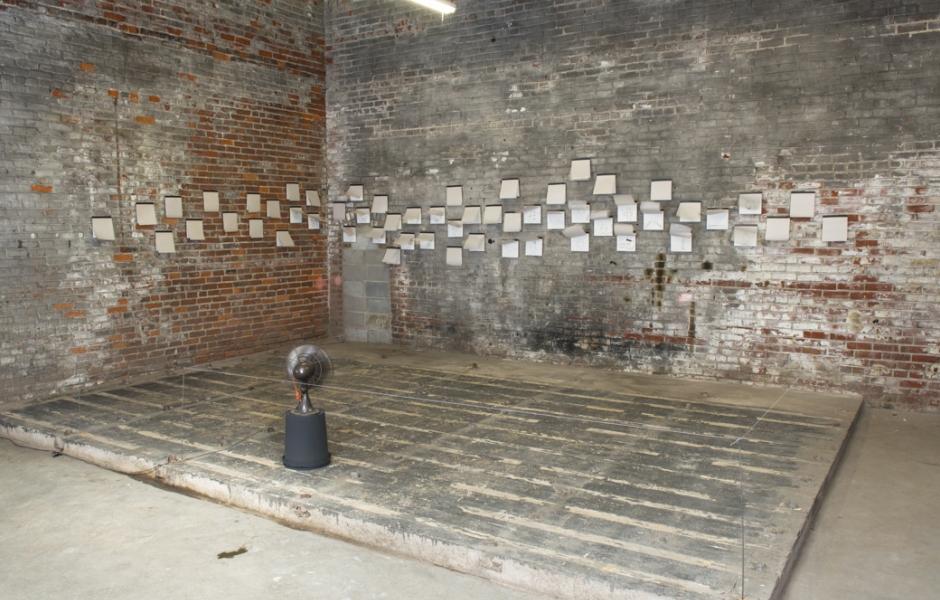 Fan blowing paper on walls