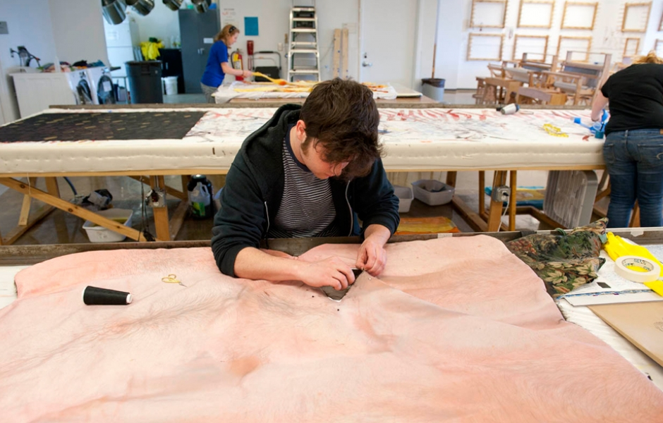 male student sewing suede