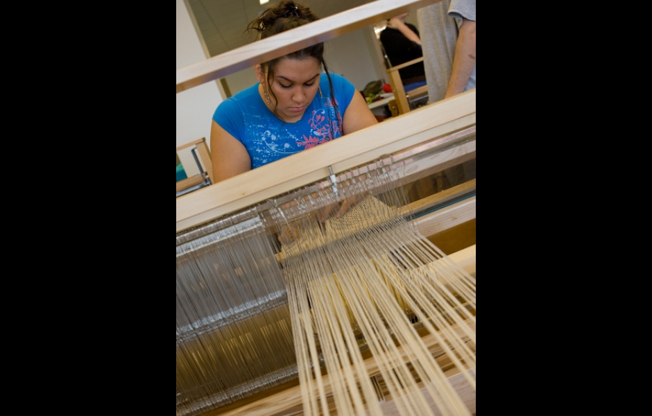 female student at weaving loom