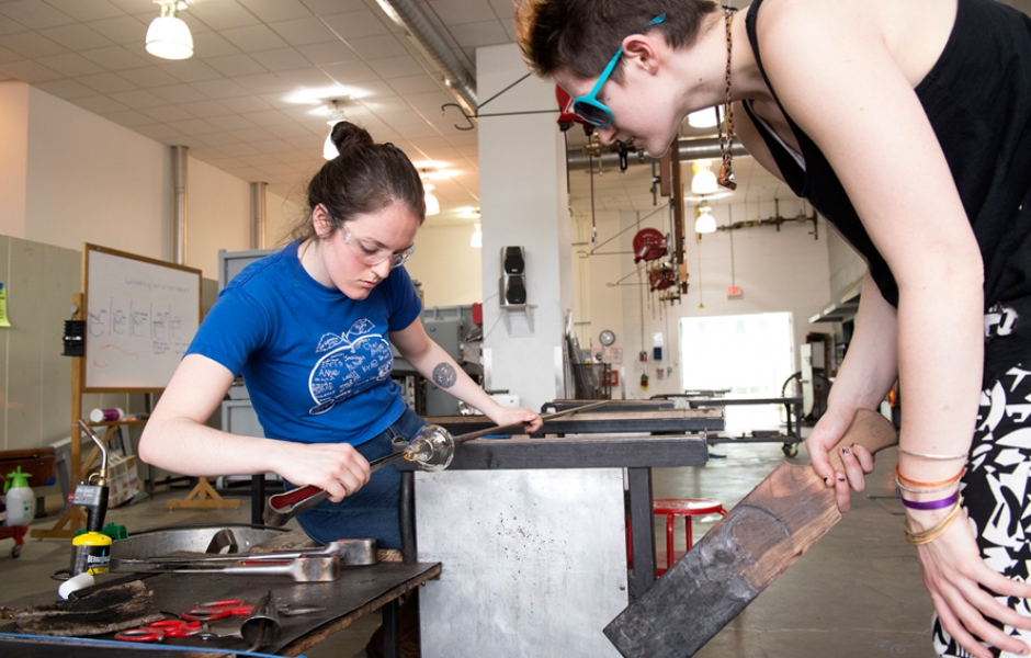 two female students working on shaping glass