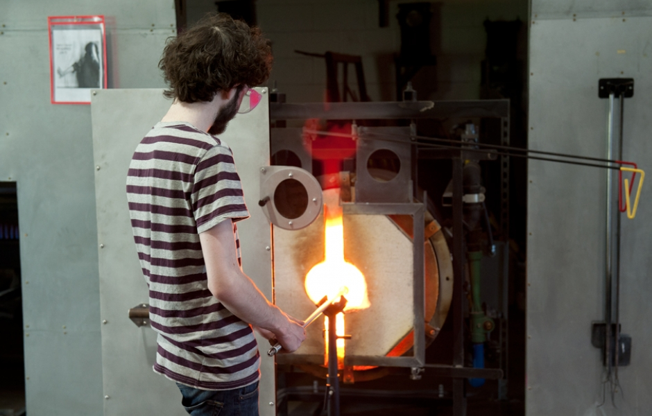 male student standing in front of kiln