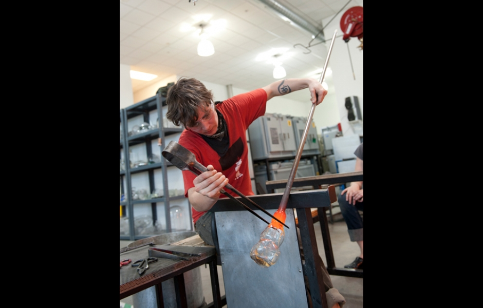 student shaping blown glass