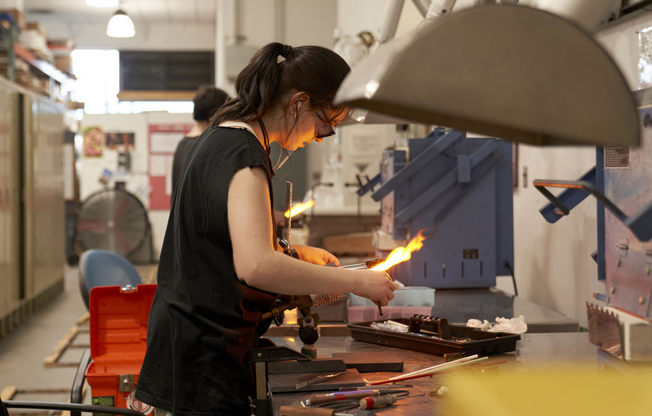 female student melting glass over flame