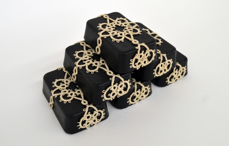 black soap bars with cream doilies around them