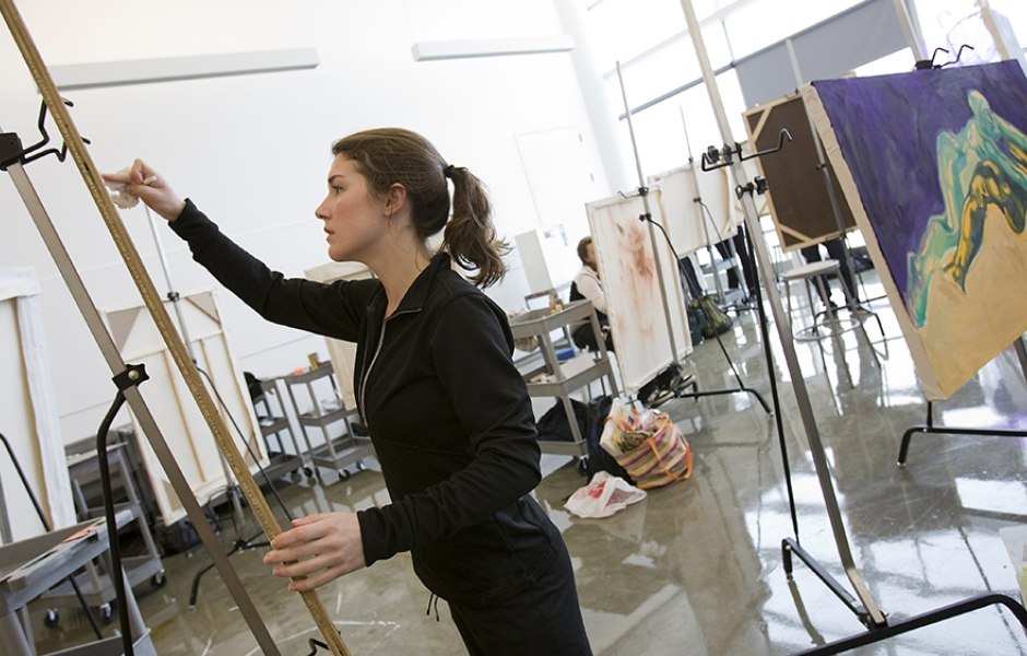 student works on painting in studio