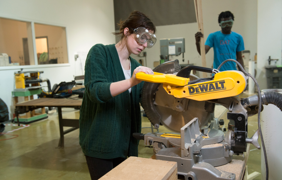 student uses saw to work on sculpture project
