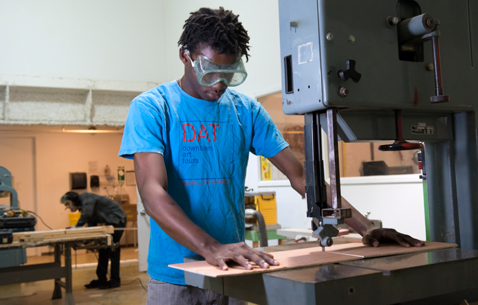 student uses bandsaw to work on sculpture project