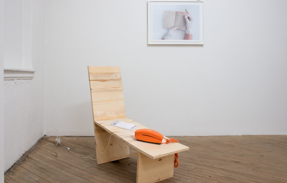 Installation of wooden sculpture, telephone, and photographic image