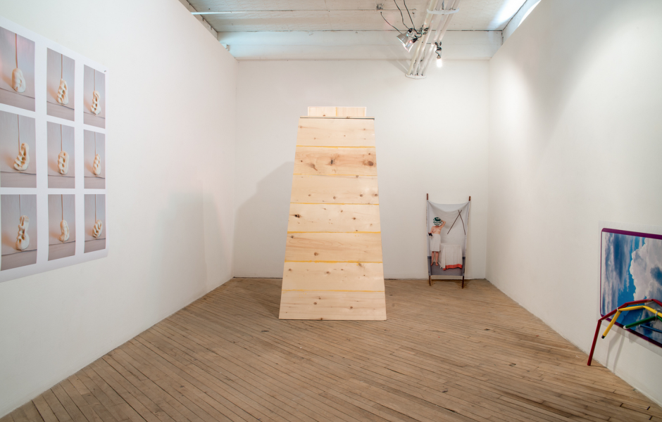 Installation of wooden sculpture and photographic images