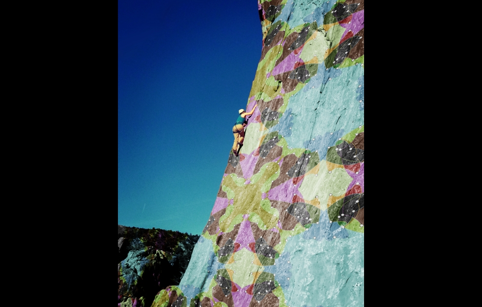 a multi-colored quilt pattern pasted on a cliff face