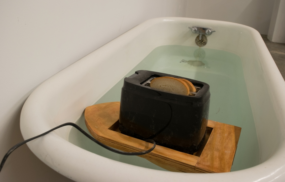 A toaster toasting floating on a boat in a bathtub